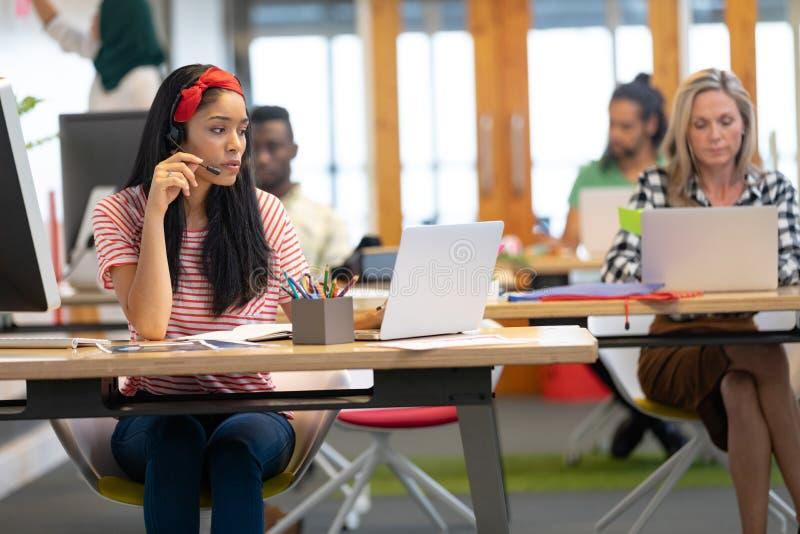Kvinnlig kundtjänstledare som talar på hörlurar med mikrofon och arbetar på bärbara datorn i ett modernt kontor arkivbilder