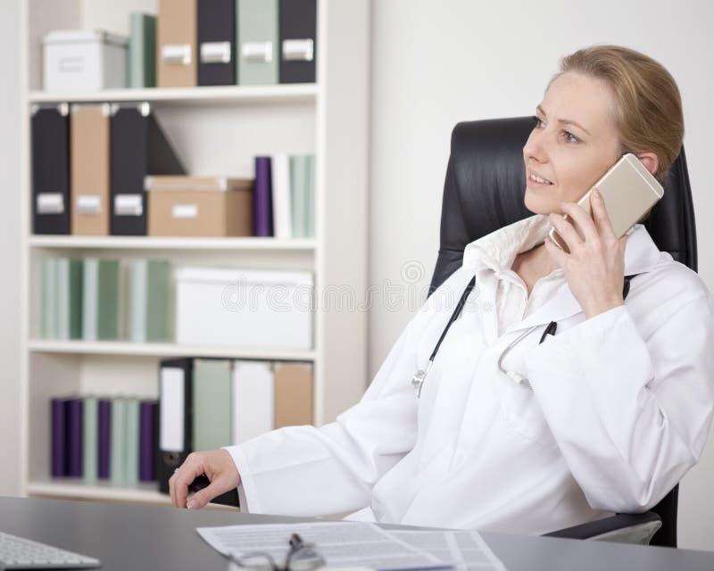 Kvinnlig läkare på stol som kallar på mobiltelefonen fotografering för bildbyråer