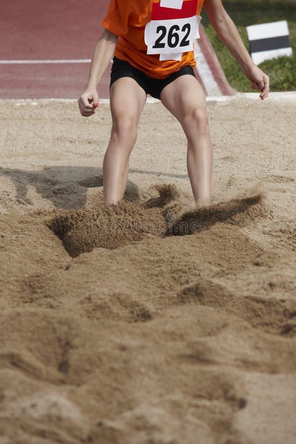 Kvinnlig längdhoppkonkurrens med kvinnan som faller i sanden arkivfoton