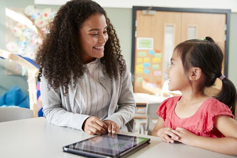Kvinnlig lärare för begynnande skola som arbetar en på en med en kinesisk skolflicka som sitter på en tabell i ett klassrum genom arkivfoto