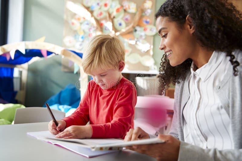 Kvinnlig lärare för begynnande skola som arbetar en på en med en ung vit skolpojke som sitter på en tabell i en klassrumhandstil, royaltyfria foton