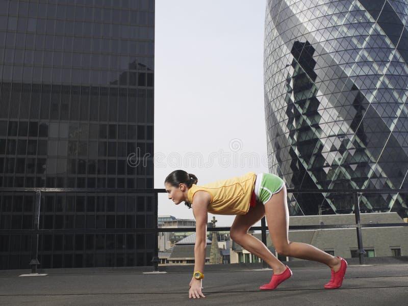 Kvinnlig löpare i startposition mot byggnader royaltyfri foto