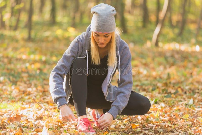 Kvinnlig löpare som binder henne skor och utanför förbereder sig för en körning arkivfoton