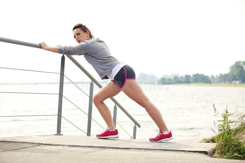Kvinnlig löpare som sträcker för körning arkivbilder