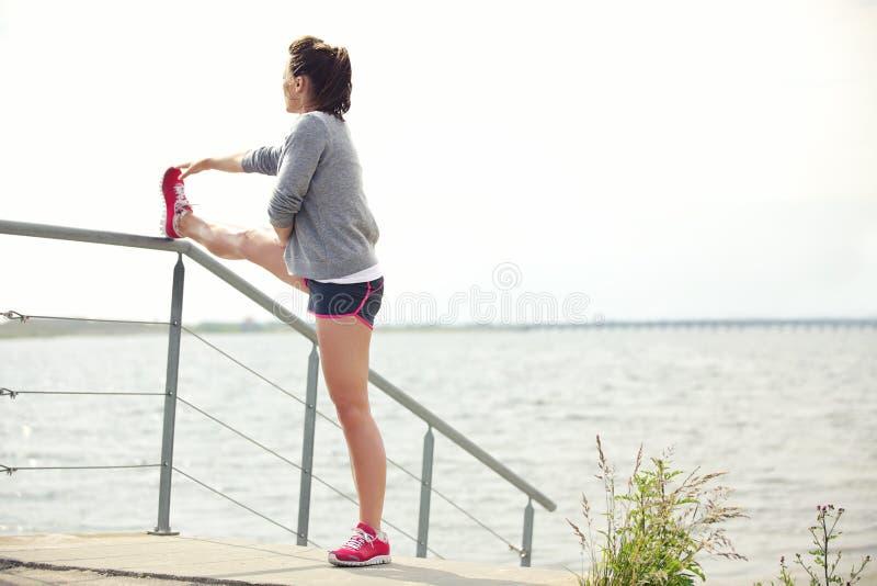 Kvinnlig löpare som sträcker henne ben royaltyfri bild