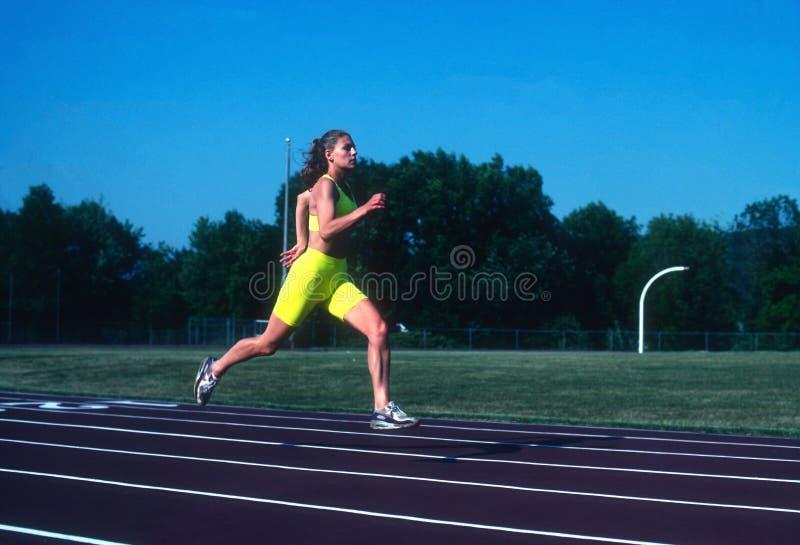 Kvinnlig löparesprinter som övar och utbildar arkivfoton