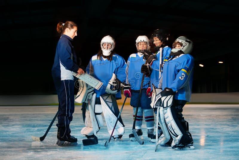 Kvinnlig lagledare som granskar spelplanen med hockeylaget royaltyfria bilder