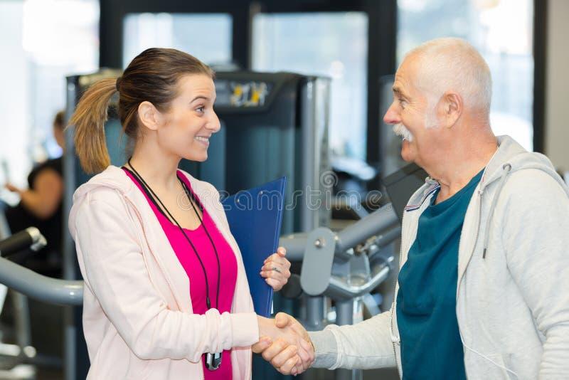 Kvinnlig lagledare som möter klienten för hög man på idrottshallklubban royaltyfri bild