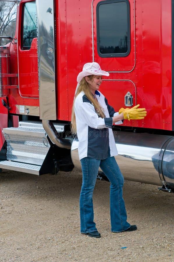 Kvinnlig lastbilschaufför som tar på sig handskar för att inspektera en stor rigg arkivbilder