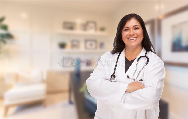 Kvinnlig latinamerikansk doktor eller sjuksköterska Standing i hennes kontor arkivfoton