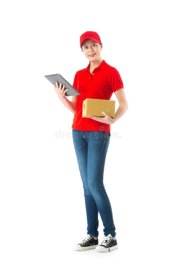 Kvinnlig leveranstjänsteman som använder den digitala minnestavlan fotografering för bildbyråer