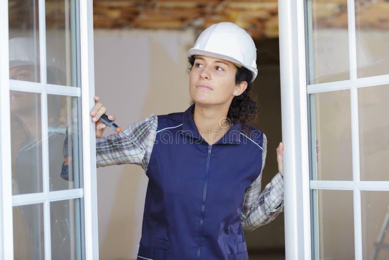 Kvinnlig leverantörinnehavskruvmejsel som ut ser från dubbla glasade fönster royaltyfri bild