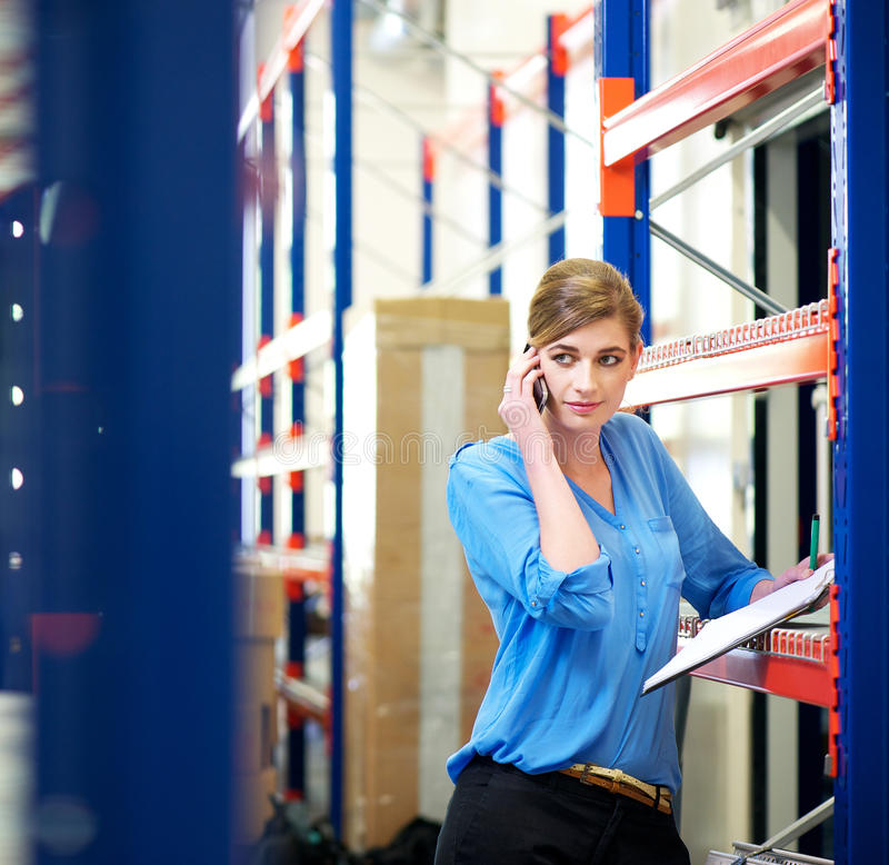 Kvinnlig logistikanställd på telefonen och kontrollerainventariet arkivfoto