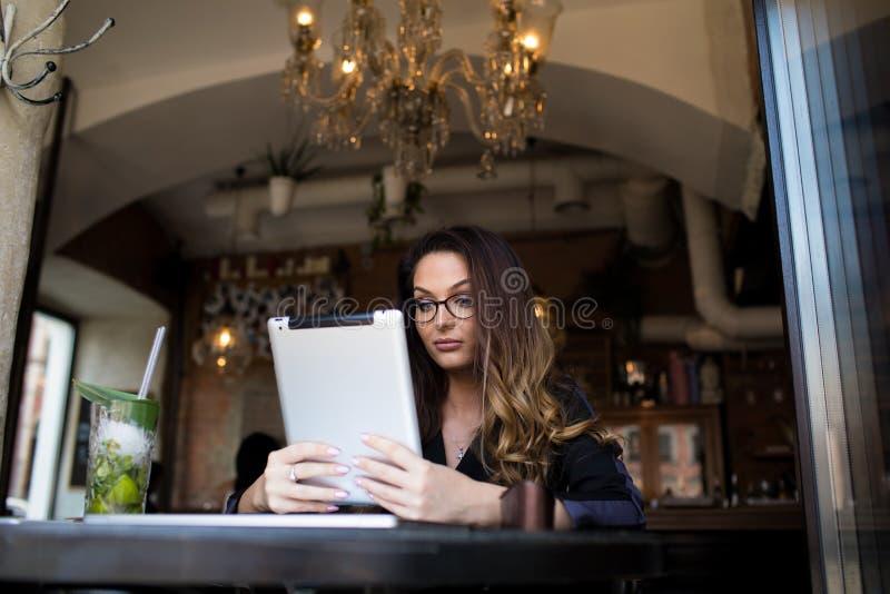 Kvinnlig lyckad ägareläsningnyheterna på webbplats via den digitala minnestavlan under vilar i restaurang royaltyfria foton