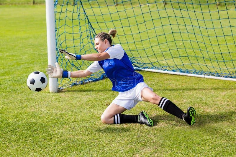 Kvinnlig målvakt som sparar ett mål arkivfoto