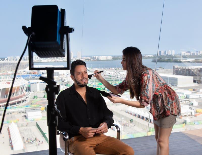 Kvinnlig makeupkonstnär på arbete på televisionstudion arkivfoto