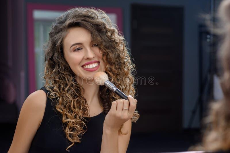 Kvinnlig makeupkonstnär som applicerar borsten arkivbilder