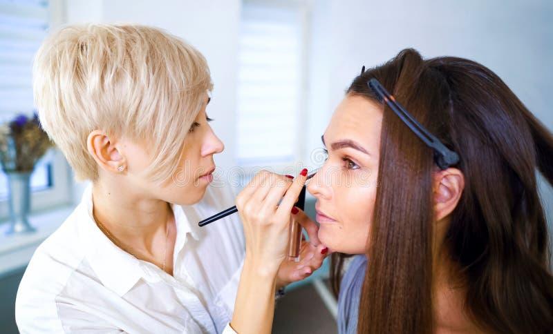 Kvinnlig makeupkonstnär som gör yrkesmässig makeup för ung brunettkvinna på skönhetsalongen royaltyfri foto