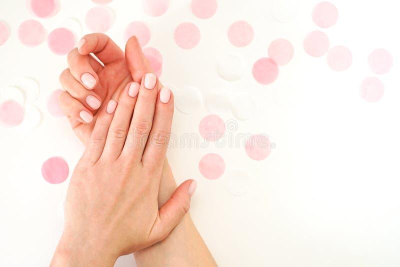 Kvinnlig manikyr för stilfull moderiktig näck färg Händer för kvinnor s på bakgrund av festliga konfettier royaltyfria foton