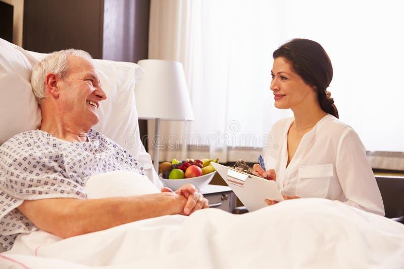 Kvinnlig manlig patient för doktor Talking To Senior i sjukhussäng arkivbilder