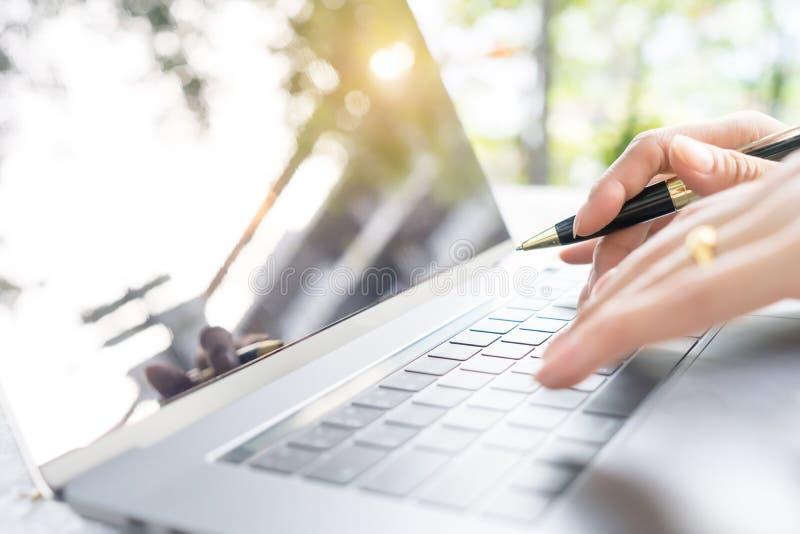 Kvinnlig maskinskrivning för hållande penna för hand på nyckel- bräde för bärbar dator på tabellen med fotografering för bildbyråer