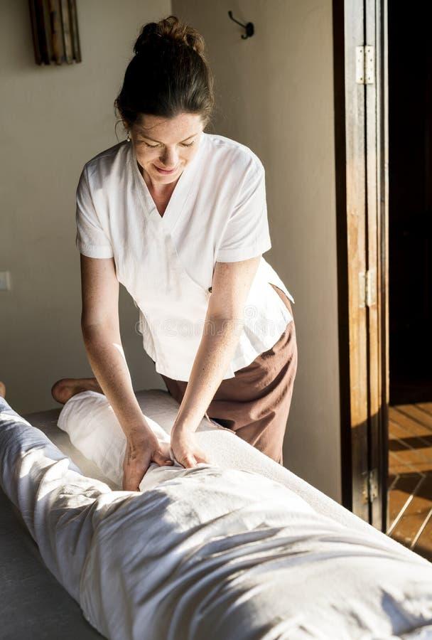 Kvinnlig massageterapeut som ger en massage på en brunnsort royaltyfri bild