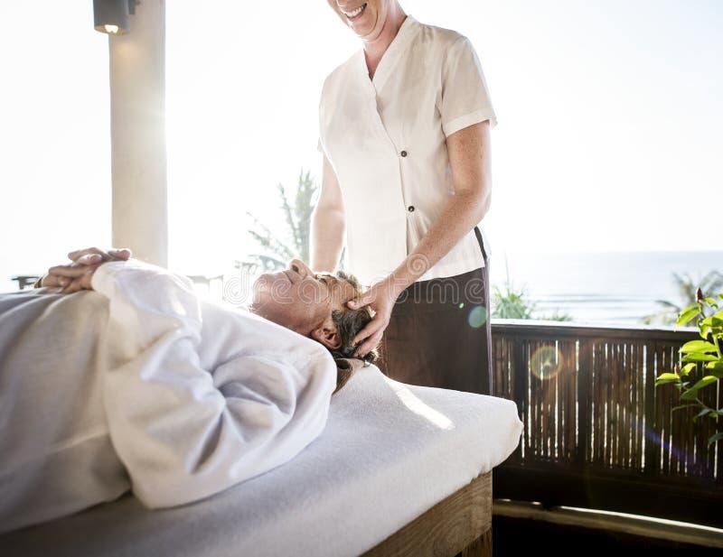 Kvinnlig massageterapeut som ger en massage på en brunnsort fotografering för bildbyråer