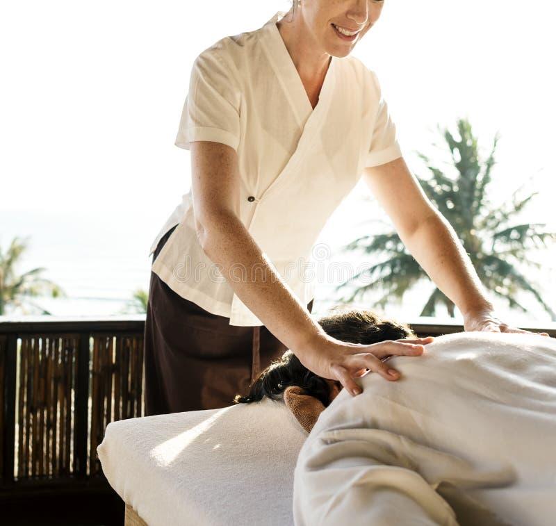 Kvinnlig massageterapeut som ger en massage på en brunnsort royaltyfria bilder