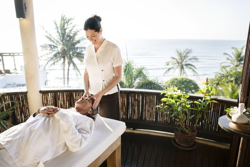 Kvinnlig massageterapeut som ger en massage på en brunnsort arkivbild