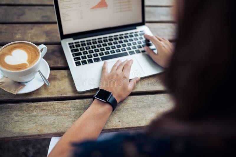 Kvinnlig med smartwatch genom att använda bärbara datorn på kafét arkivfoto