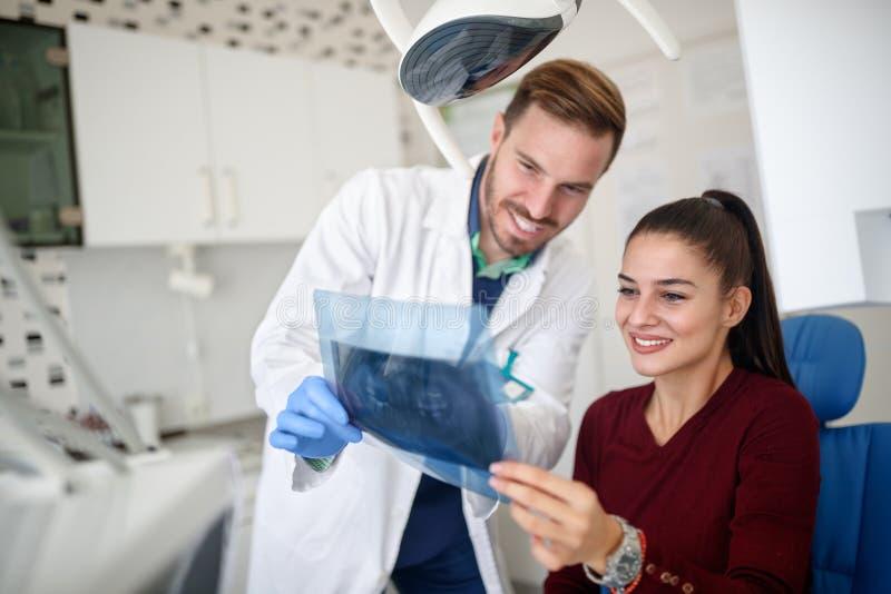 Kvinnlig med tandläkaren som ser hennes tänder på röntgenstråle royaltyfri foto