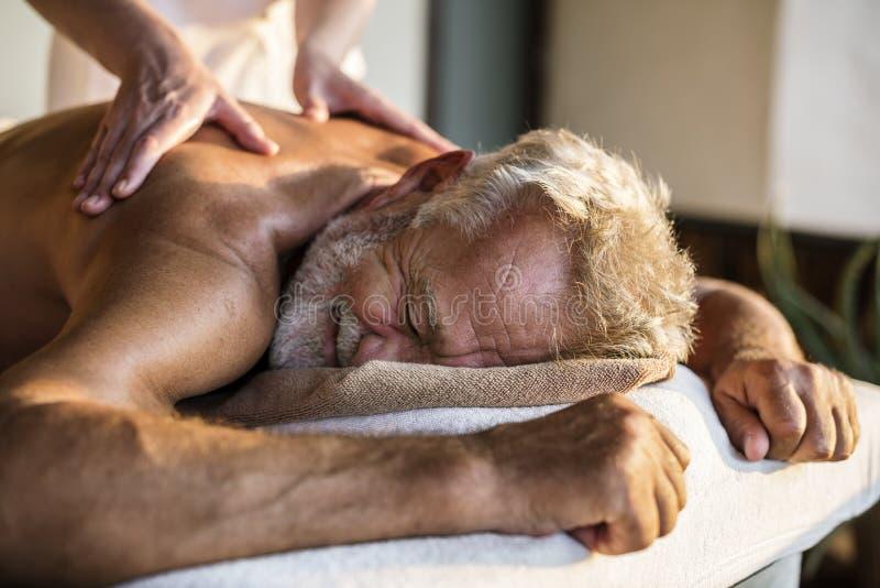 Kvinnlig meddelandeterapeut som ger en massage på en brunnsort arkivfoton