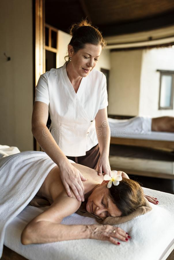 Kvinnlig meddelandeterapeut som ger en massage på en brunnsort arkivfoto