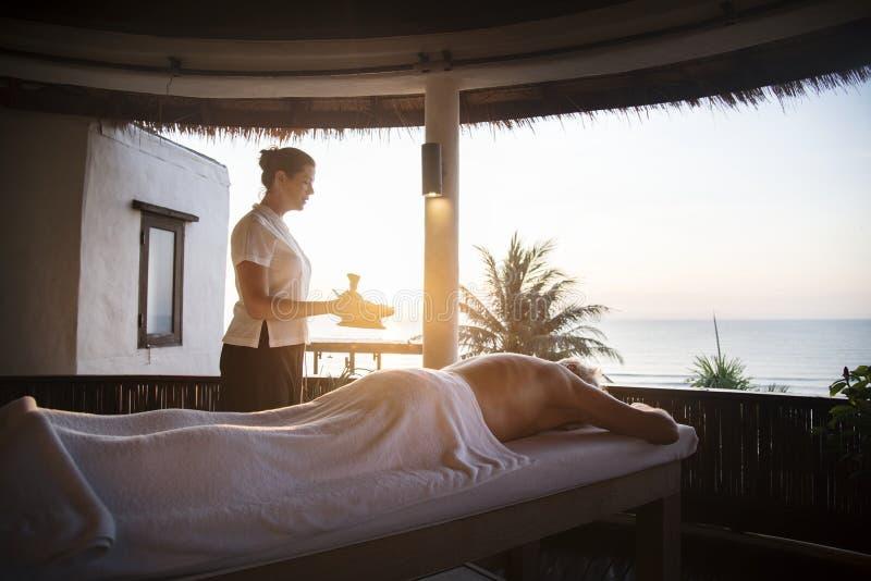 Kvinnlig meddelandeterapeut som ger en massage på en brunnsort royaltyfri fotografi