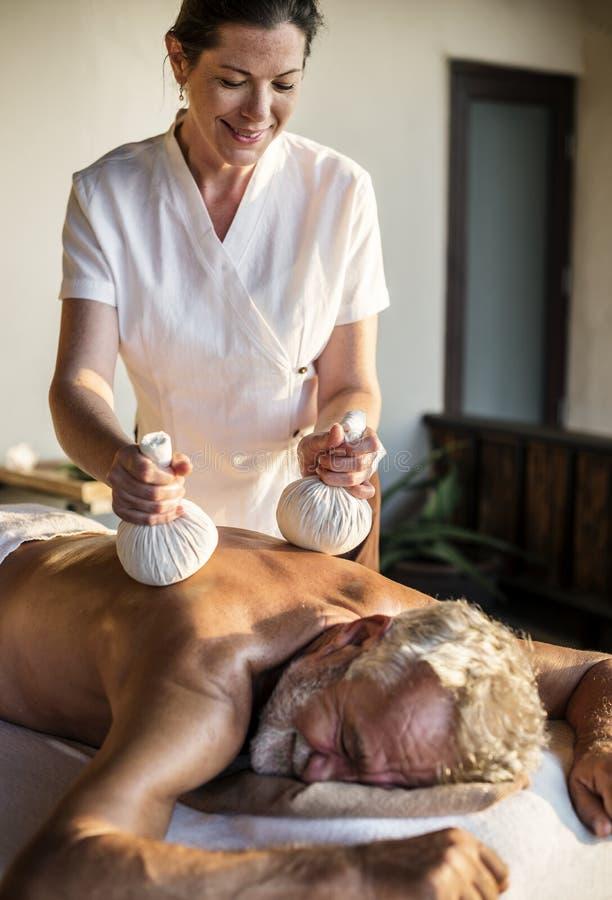 Kvinnlig meddelandeterapeut som ger en massage på en brunnsort fotografering för bildbyråer