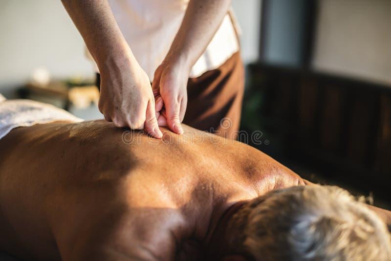 Kvinnlig meddelandeterapeut som ger en massage på en brunnsort arkivbilder