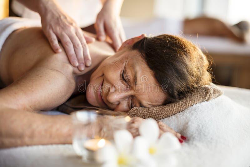 Kvinnlig meddelandeterapeut som ger en massage på en brunnsort royaltyfri bild