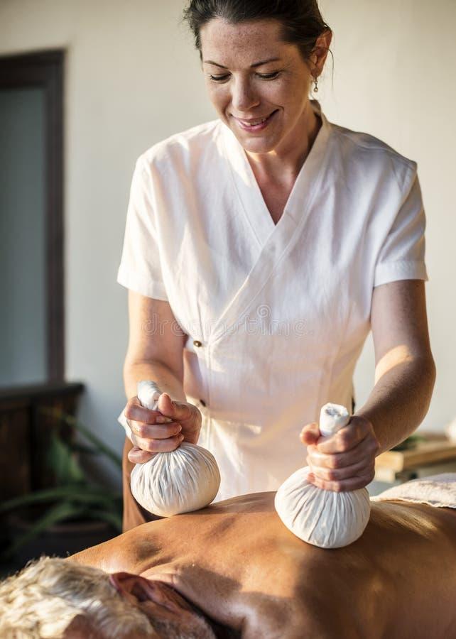 Kvinnlig meddelandeterapeut som ger en massage på en brunnsort royaltyfria foton