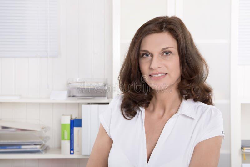 Kvinnlig medelålders doktor i ståendesammanträde på skrivbordet royaltyfria bilder