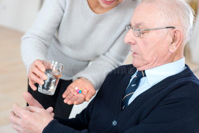 Kvinnlig medicinsk assistent som ger äldre tålmodigt preventivpillerar och vatten royaltyfri bild