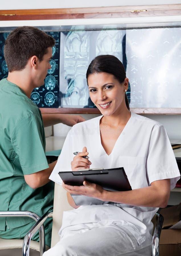 Kvinnlig medicinsk tekniker Holding Clipboard arkivfoto