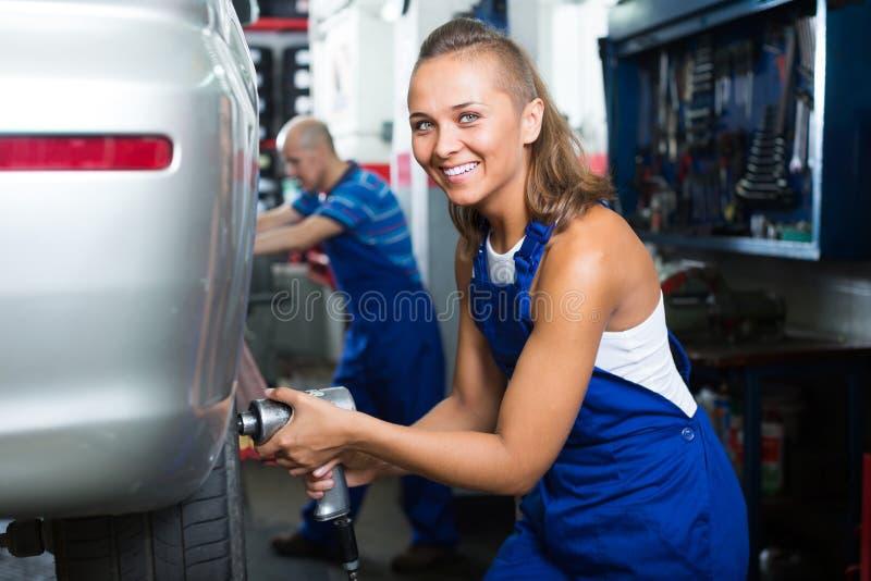 Kvinnlig mekaniker som arbetar på bildäckservice royaltyfri bild