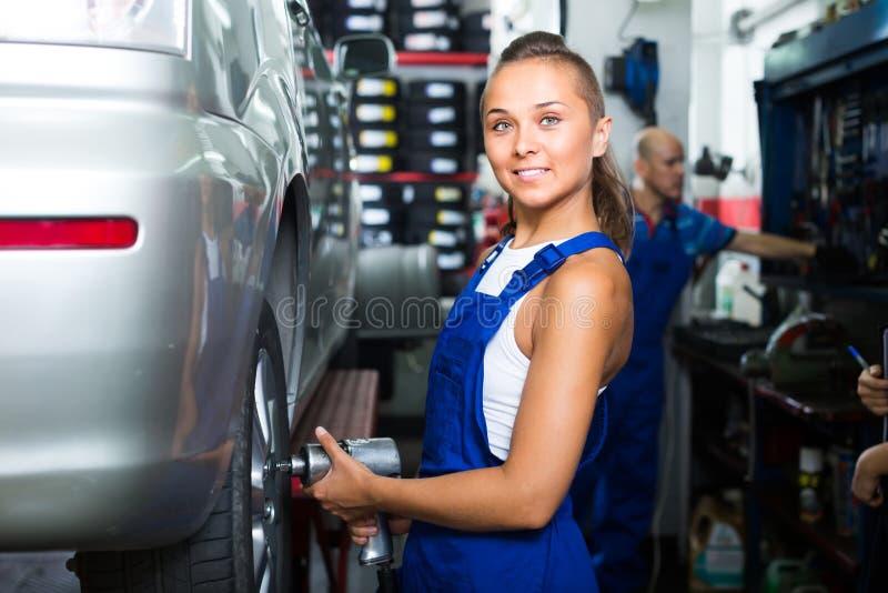 Kvinnlig mekaniker som arbetar på bildäckservice fotografering för bildbyråer