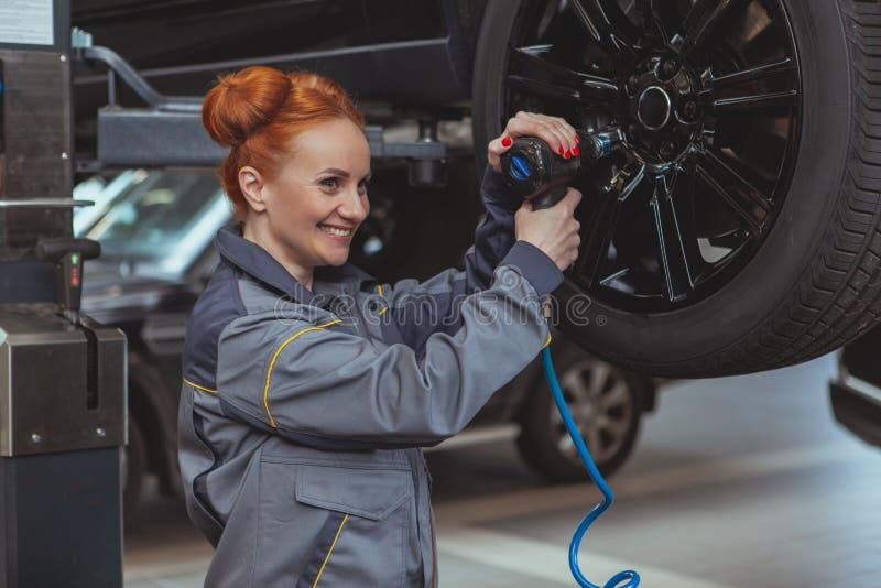 Kvinnlig mekaniker som arbetar p? bilservicestationen arkivfoton