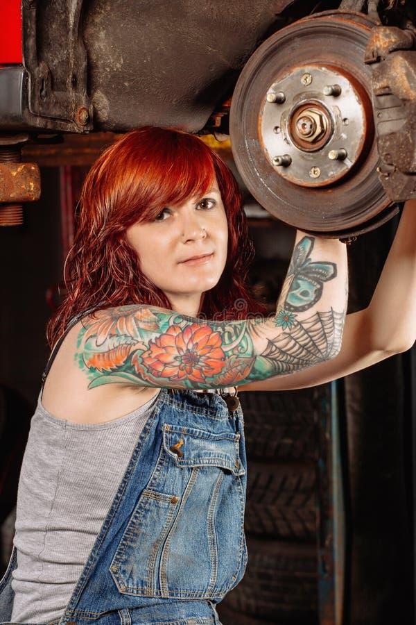 Kvinnlig mekaniker som arbetar under bilen arkivfoton