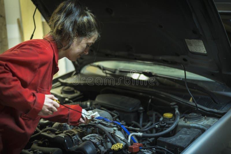 Kvinnlig mekaniker som kontrollerar den olje- nivån av en bil royaltyfri bild