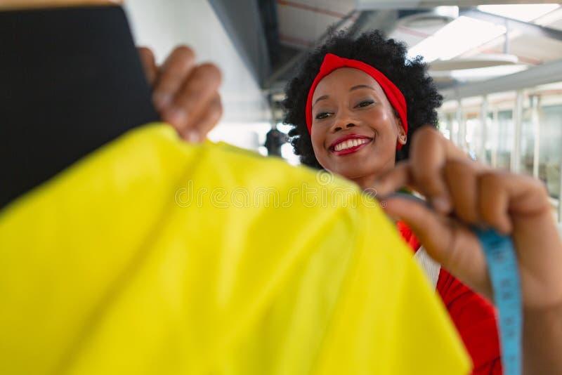 Kvinnlig modeformgivare som använder mäta bandet på en skyltdocka i designstudio arkivfoto