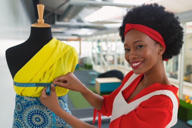 Kvinnlig modeformgivare som använder mäta bandet på en skyltdocka i designstudio royaltyfri bild