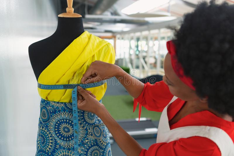 Kvinnlig modeformgivare som använder mäta bandet på en skyltdocka i studio royaltyfria foton
