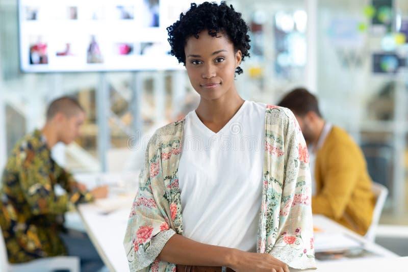 Kvinnlig modeformgivare som i regeringsställning lutar på en tabell på konferensrum arkivbild